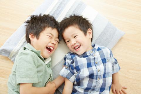 Brothers lying on pillow laughing
