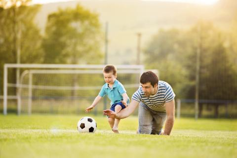 Man and young boy play with a soccer ball on a field.