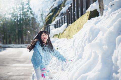 Young girl runs down snow-lined street with a smile on her face.