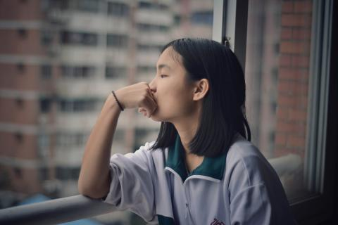 Teenaged girl looks morosely out the window of a high rise apartment.