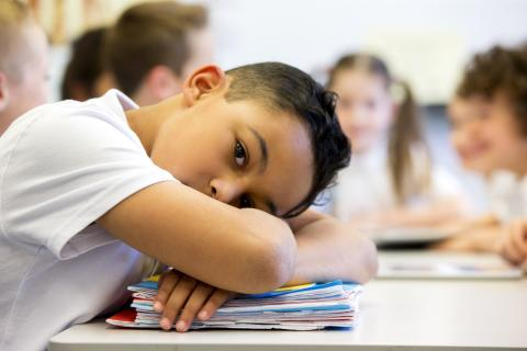 Young boy falls asleep at school.