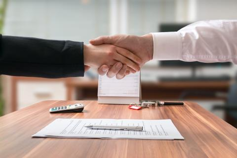 Two adults reach an agreement and shake hands.
