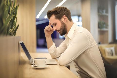 Man looks over his computer with a stressful expression.