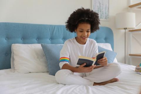 A young girl reads quietly in bed.