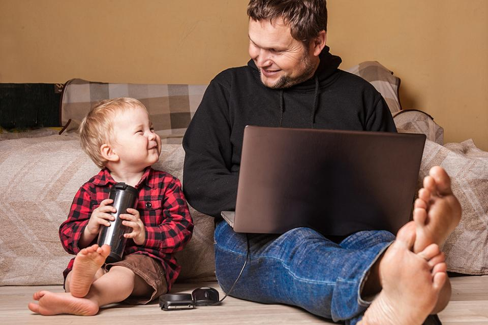 Father and son sitting side by side while dad works on laptop