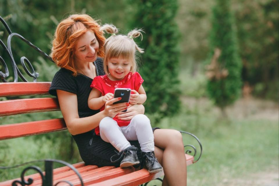 Mom holds daughter on park bench as they look at a phone together