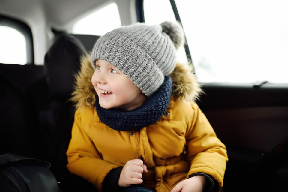 Bundled-up little boy in the backseat of a car, on his way to a parent's house.
