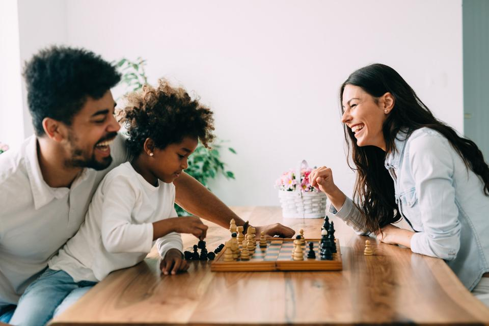 Co-parents play chess with their child together at a dining room table.